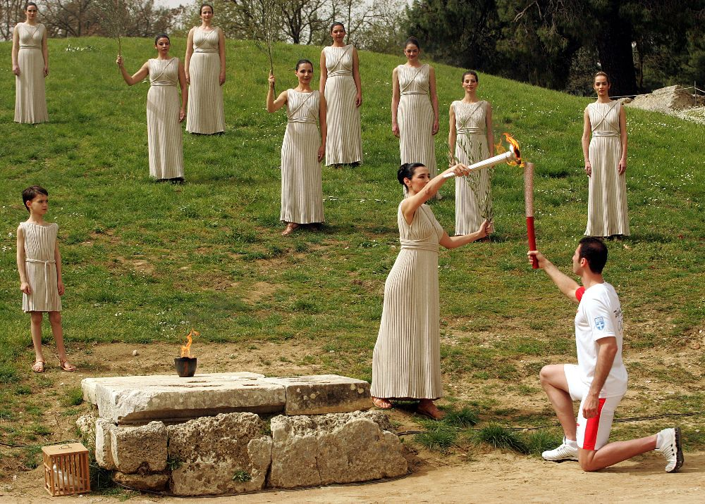Actress Maria Nafpliotou (C) in the role of the High Priestess lights the torch of the Olympic Flame of the first torchbearer Alexandros Nikolaidis , Olympic winner of Tae Kwo Do , during the rehearsal of Lightning Ceremony of the Olympic Flame for Beijing summer Olympics, in front of Hera Temple in Ancient Olympia,  23 March 2008. EPA/ORESTIS PANAGIOTOU